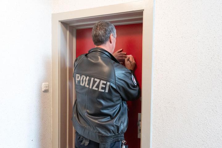 Ein Polizist versiegelt eine Tür am Tatort.