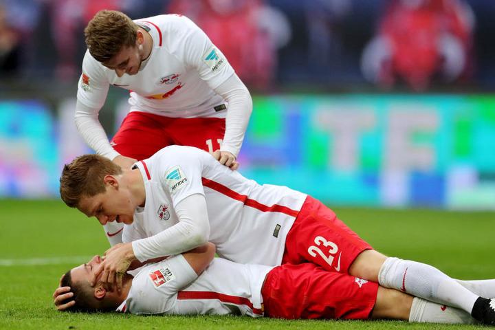 Leipzigs Marcel Halstenberg (m.) und Timo Werner (hinten) kümmern sich nach dem 4:0 um den verletzten Torschützen Diego Demme.