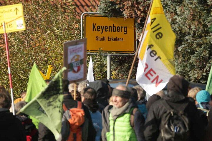 Demonstranten stehen mit Flaggen vor dem Ortseingangsschild des Dorfes Keyenberg.