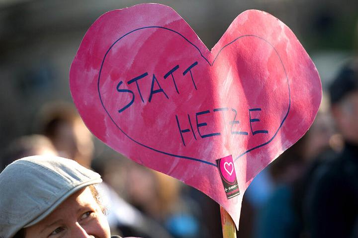 """""""Herz statt Hetze"""" steht auf einem selbstgebastelten Herz-Banner."""