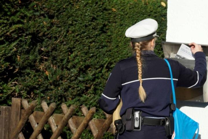 Eine Polizistin informiert Anwohner über den bevorstehenden DNA-Massentest.