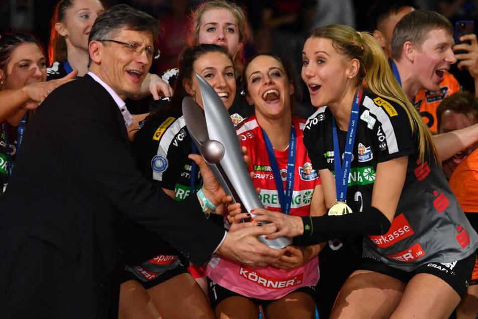 Mareen von Römer, Lenka Dürr und Lena Stigrot (von links) bekommen von DVV-Präsident René Hecht den Pokal überreicht.