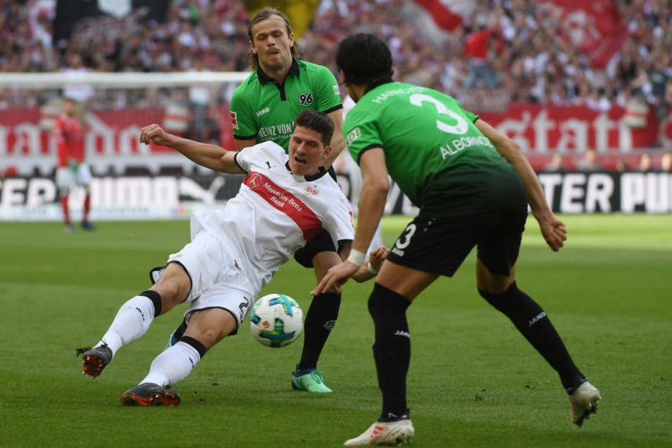 Stuttgarts Mario Gomez (m.) im Zweikampf mit Hannovers Iver Fossum (l.) und Miiko Albornoz.