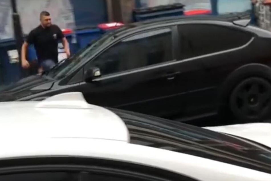 Der unbekannte Mann läuft auf das Auto zu und versucht die Fahrertür zu öffnen. Das gelingt ihm nicht.