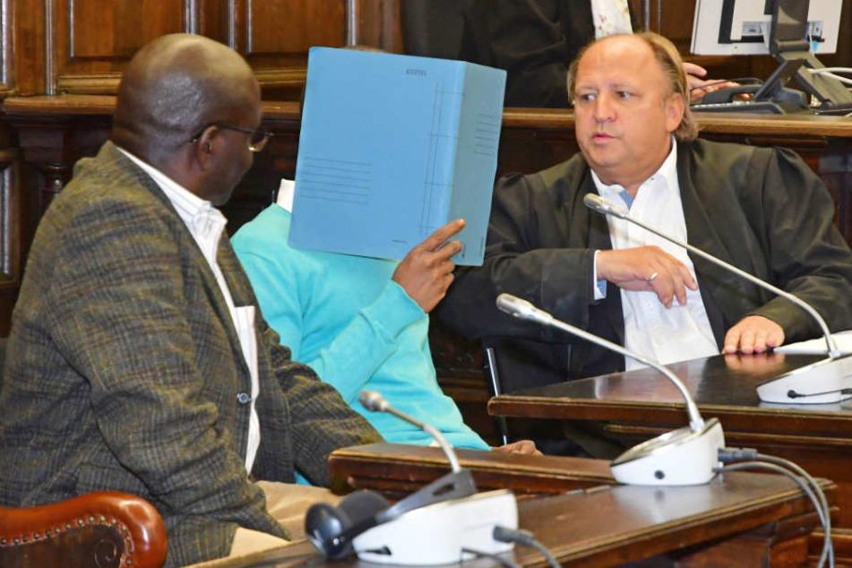 Der Angeklagte versteckt sich zwischen seinem Anwalt und einem Dolmetscher hinter einer Mappe.
