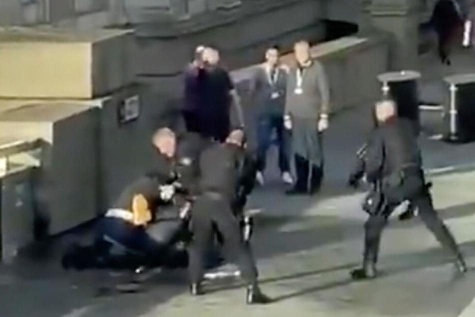 Auf der London Bridge umstellen bewaffnete Polizisten den auf dem Boden liegenden mutmaßlichen Attentäter.