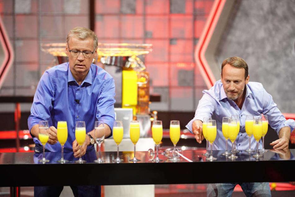 Wer ist schneller? Günther Jauch und Wotan Wilke Möhring sollen möglichst fix Gläser mit Orangensaft füllen und auf einen Tisch stellen.