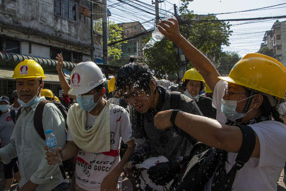 Man pours water on fellow protester to reduce the effect of teargas during the military coup demonstrations..