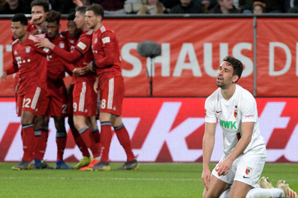 Rani Khedira (r) kniet auf dem Rasen, während die Spieler von München über das 2:3 jubeln.