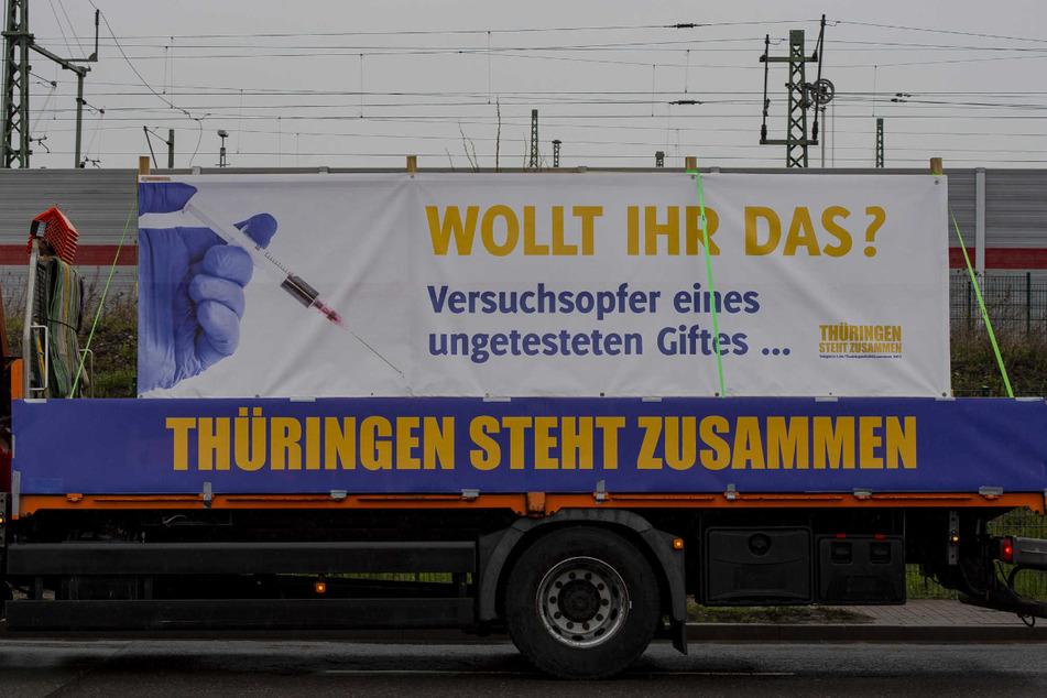 """""""Wollt ihr das? Versuchsopfer eines ungetesteten Giftes"""" steht auf einem Plakat des Bündnisses """"Thüringen steht zusammen"""". Gleichzeitig wird der Impfstoff als Gefährlich und nicht als rettend gesehen."""