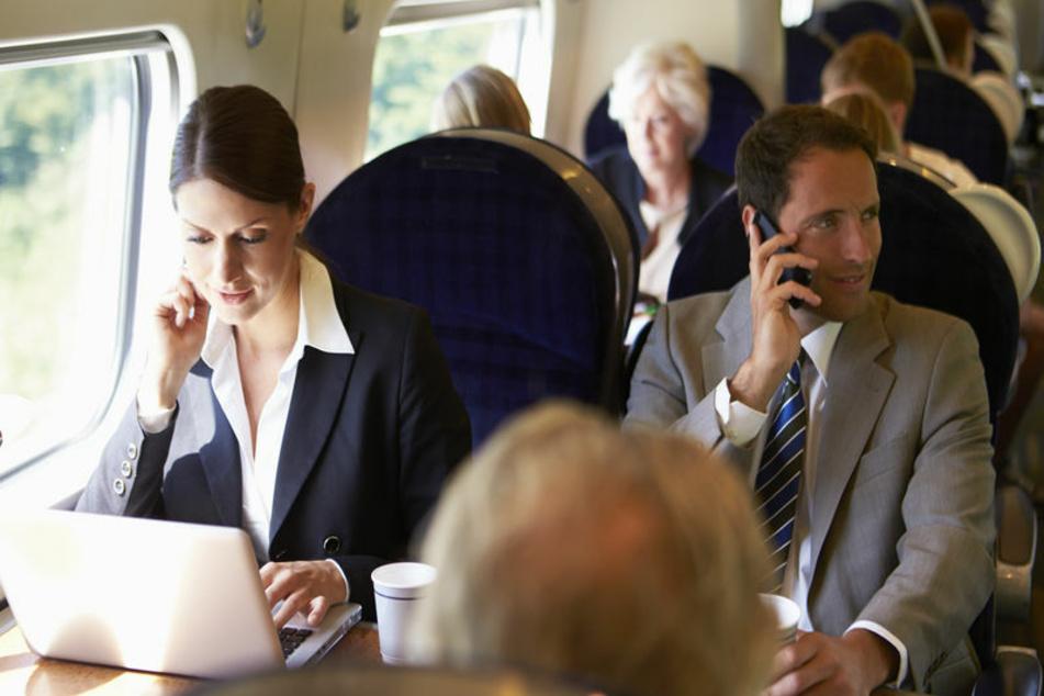 Geschäftsleute reisen in einem Zug. (Symbolbild)