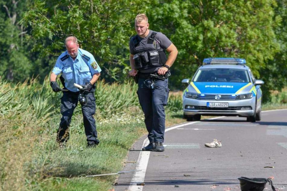 Polizisten sichern Spuren an der Unfallstelle bei Wanzleben.
