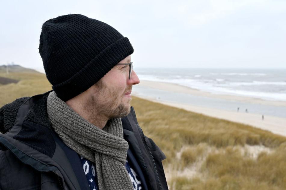 Agrarminister Jan Philipp Albrecht (Bündnis 90/Die Grünen) steht auf der Nordseeinsel Sylt am Strand.