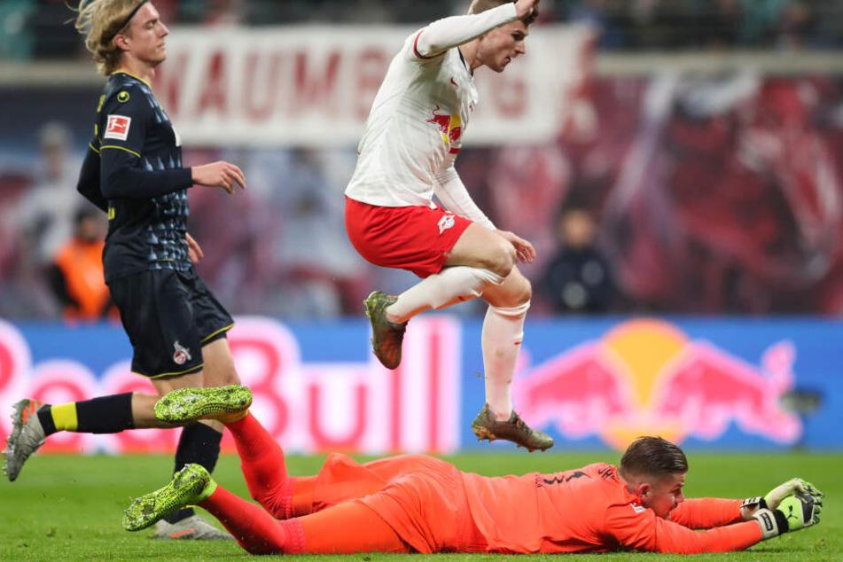 Timo Werner (M) springt nach seinem Torschuss zum 1:0 über Kölns Torwart Timo Horn (liegend), dahinter Kölns Sebastiaan Bornauw.