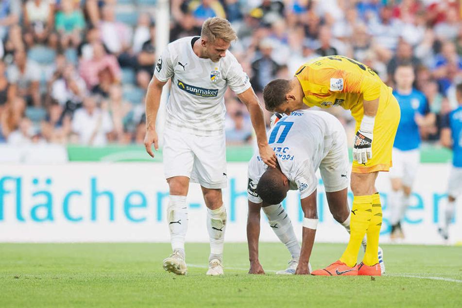 Pierre Fassnacht (links) und Torwart Jo Coppens (Jena, rechts) versuchen Marian Sarr (Jena) nach dessen zweitem Eigentor zum 2:1 für Ingolstadt aufzumuntern. Nun muss der Spieler in die Oberliga rücken.