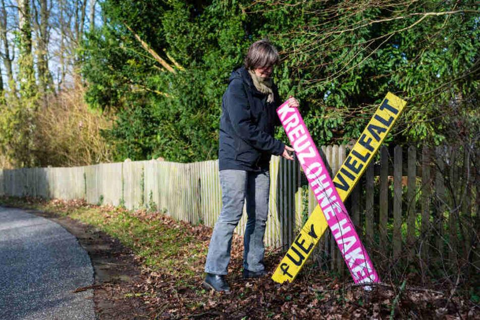 """Eine Anwohnerin stellt ein Holzkreuz mit der Aufschrift """"Kreuz ohne Haken - fuer Vielfalt"""" in Haarstorf auf."""