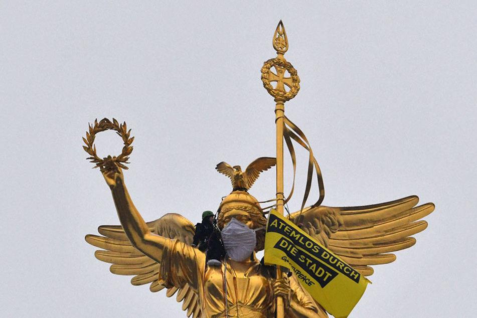 """Greenpeace-Aktivisten überziehen der Statue auf der Siegessäule in Berlin eine Atemschutzmaske. Unter dem Motto """"Atemlos durch die Stadt"""" protestierten sie gegen die Stickoxidbelastung in den Innenstädten."""
