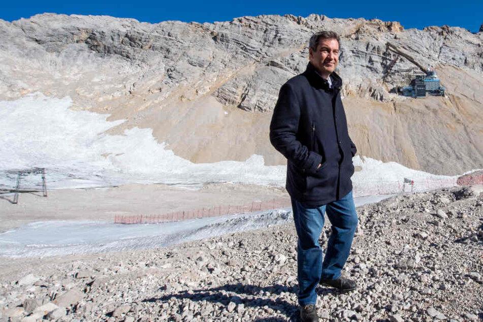 Markus Söder (CSU), Ministerpräsident von Bayern, steht bei seiner Klimatour vor dem Panorama der Zugspitzregion.