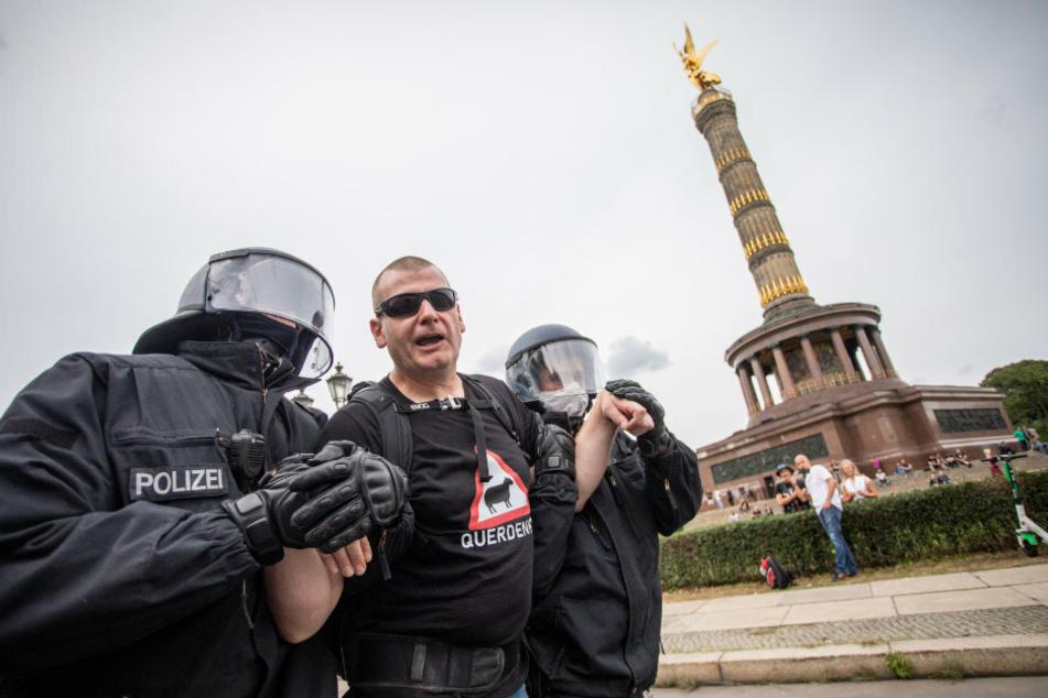 Ein Mann wird bei einem Protest gegen die Corona-Maßnahmen vor der Siegessäule von Polizisten abgeführt.