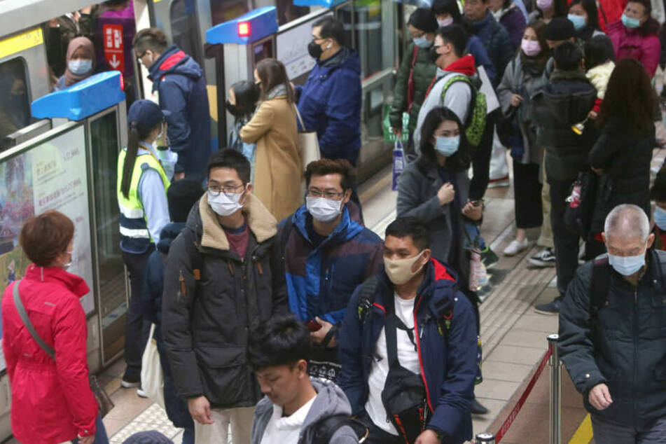 Passagiere in Taiwan tragen Mundschutz in einer U-Bahn-Station.