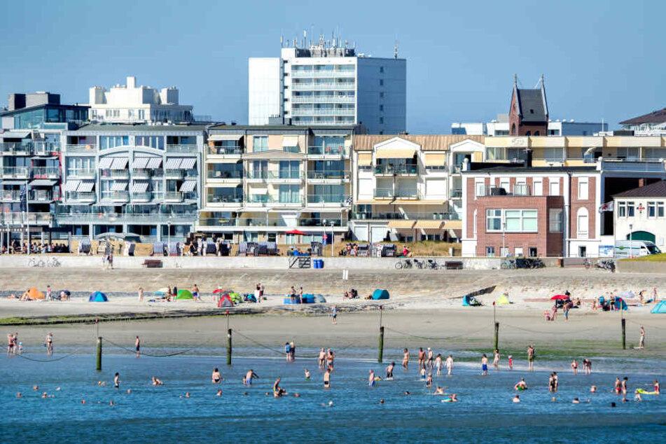 Touristen baden am Weststrand der Insel Norderney in der Nordsee.