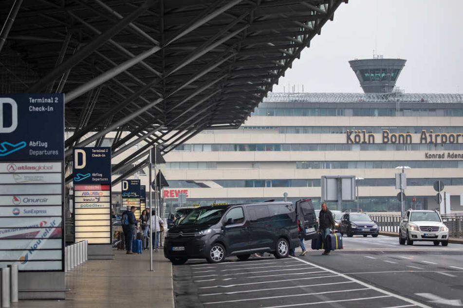 Fluggäste steigen vor dem Terminal des Flughafen Köln/Bonn aus ihren Fahrzeugen.