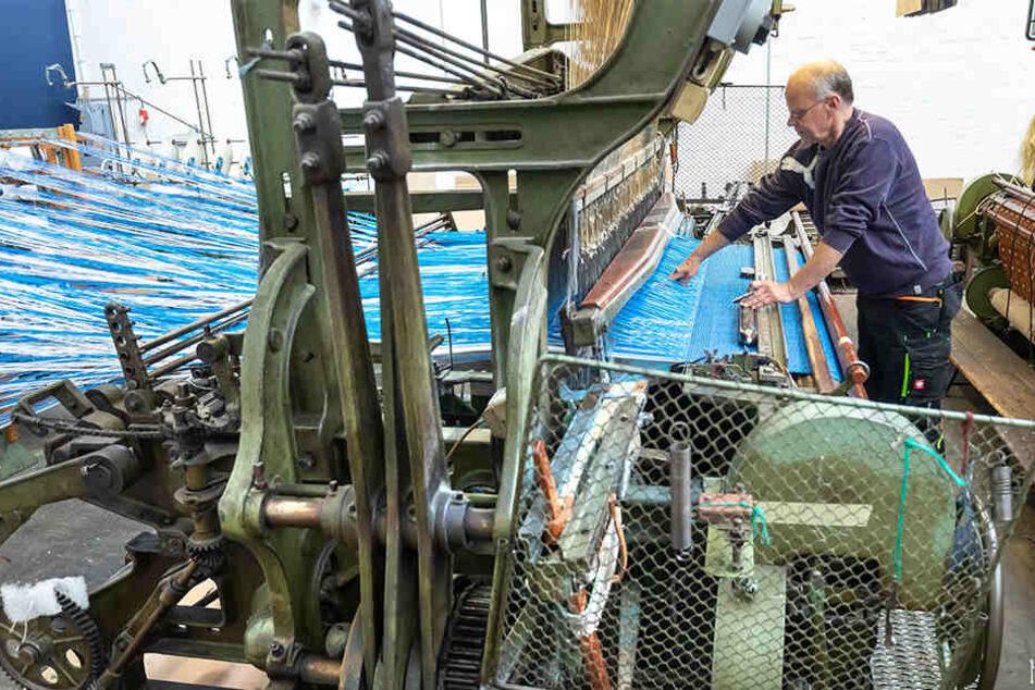 Webmeister Mario Thümer (56) verarbeitet die Spezialgarne an einem alten mechanischen Webstuhl, der robust genug für die starren Kunstgarne ist.