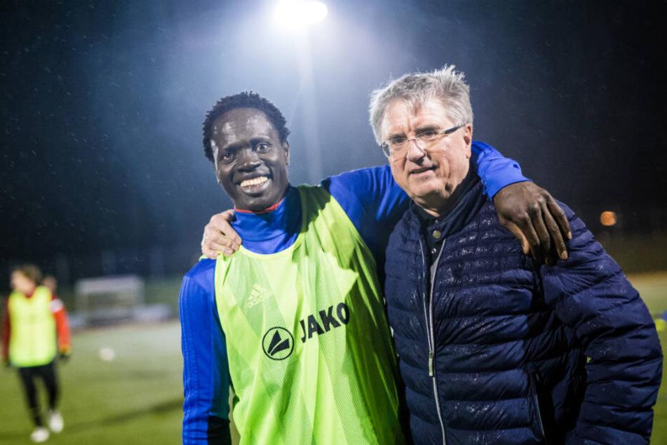Kebba Manneh (links im Bild) steht mit dem 1. Vorsitzenden des SC Lauchringen, Thomas Kummer auf dem Fußballplatz.