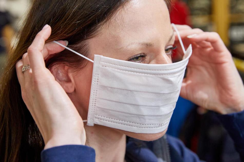 Eine Mitarbeiterin zieht sich in einem Fachgeschäft für Berufskleidung einen Mundschutz an.