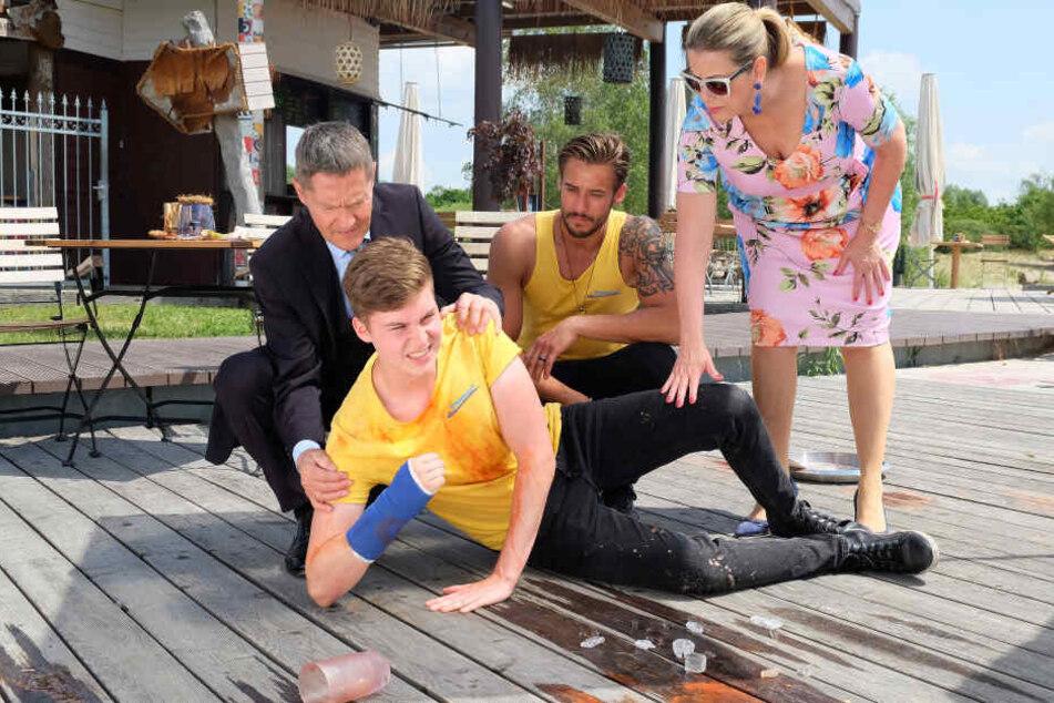 Bademeister Sasha und Dr. Rolf Kaminski (l.) helfen Sarah Marquardts gestürzten Sohn Bastian, der kurz darauf ohnmächtig wird.