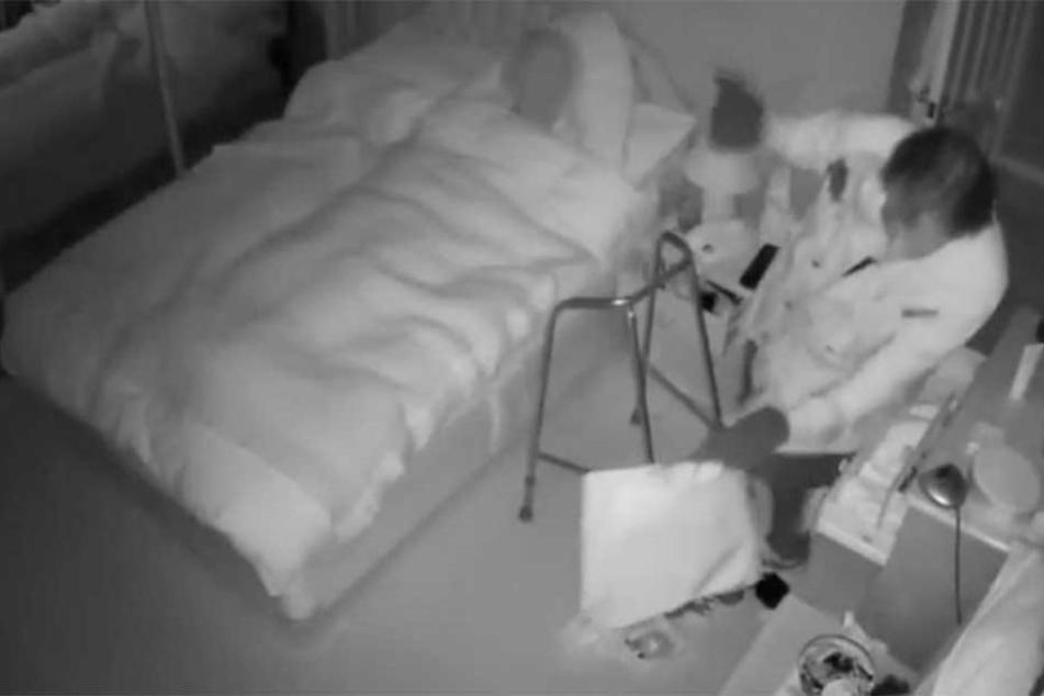 Der Einbrecher sackt Schmuck und Wertgegenstände ein, während die Besitzerin hilflos hinter ihm im Bett liegt.
