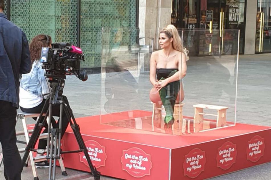 Micaela lässt sich im Glaskasten von einigen Journalisten interviewen.