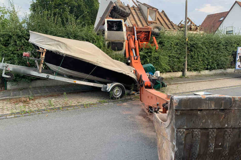 Bagger stürzt bei Abrissarbeiten um und begräbt Boot unter sich