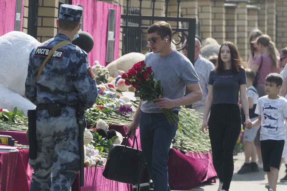 Menschen legen Blumen nach dem Angriff auf die Schule nieder.