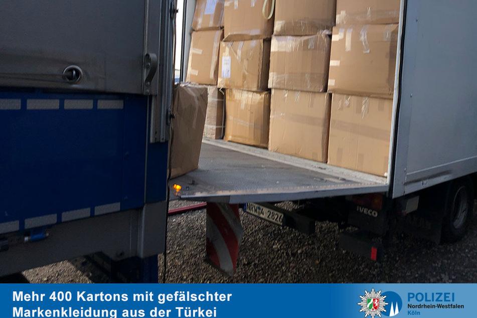 Drei Lastwagen für den Abtransport: Die Kölner Polizei fand Hunderte Kartons gefälschter Markenkleidung und stellte sie sicher.