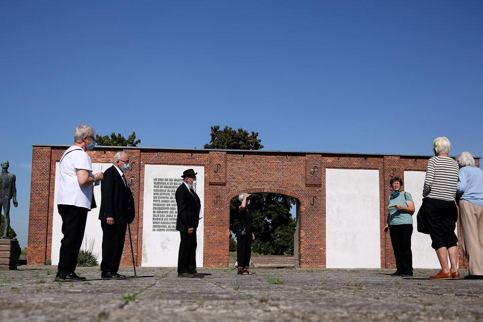 Besucher stehen vor den Resten der Feldscheune in der Gedenkstätte Feldscheune Isenschnibbe bei Garlegen.