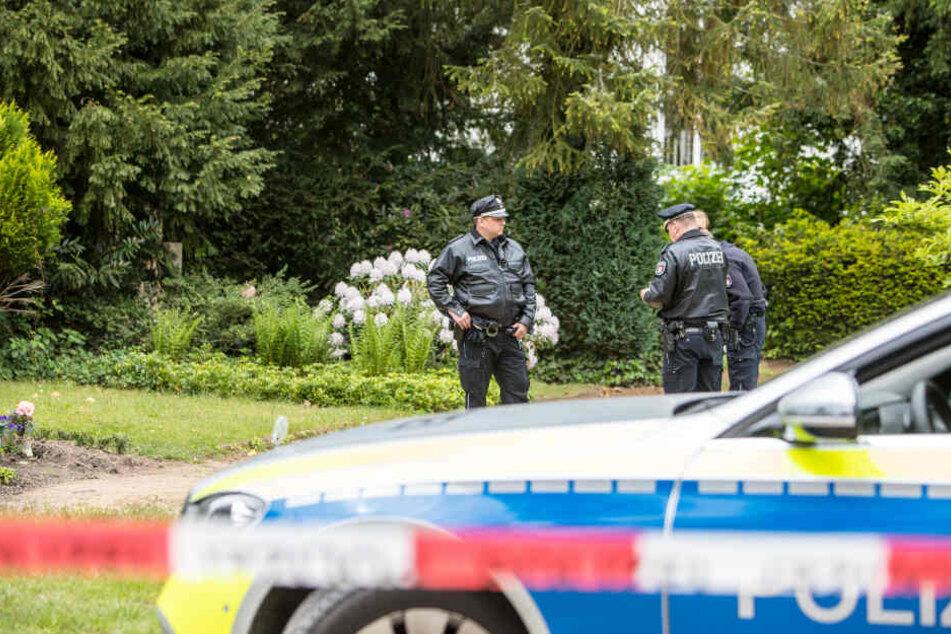 Polizisten sperren den Friedhof in Bergedorf ab, nachdem dort ein toter Mann gefunden worden war.