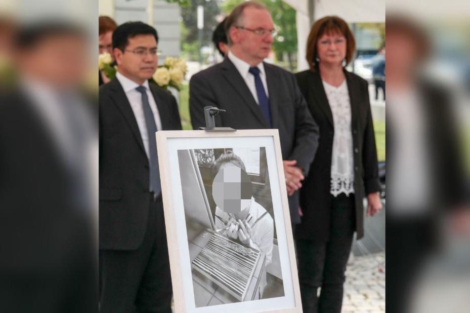 Während einer Veranstaltung in Gedenken an Yangjie Li standen Sachsen-Anhalts Ministerpräsident Reiner Haseloff (M.) mit seiner Frau Gabriele und dem chinesischen Botschaftsrat Qinghua Zhao hinter ihrem Bild.
