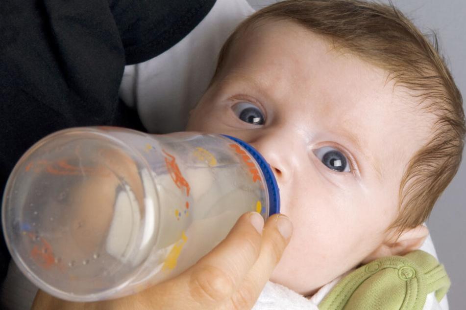 Ein Säugling trinkt aus der Flasche, während er große Kulleraugen macht.