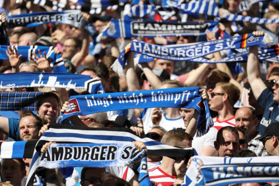 Die Fans des Hamburger SV halten ihre Schals in die Höhe.