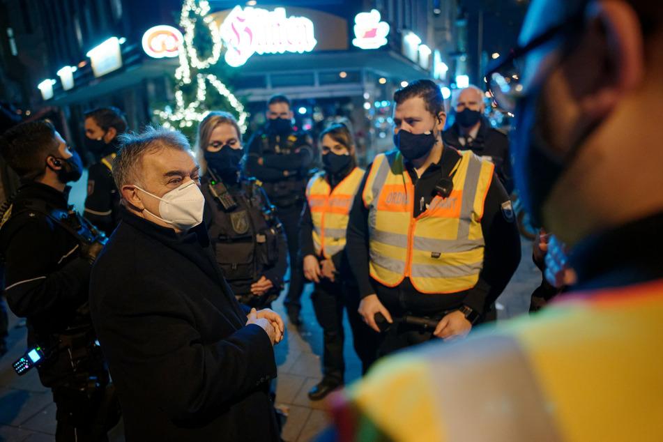 Herbert Reul (CDU, l), Innenminister von Nordrhein-Westfalen, begleitet die Kölner Polizei bei einer Corona-Streife durch das Stadtgebiet.