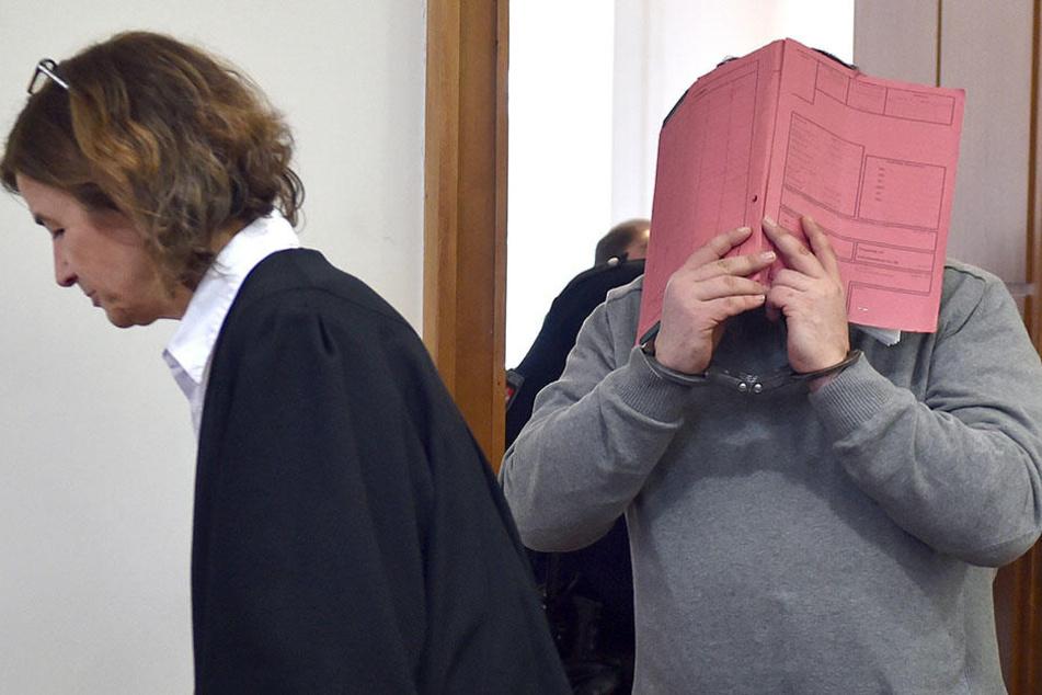 Der ehemalige Krankenpfleger Niels H. versteckt sein Gesicht hinter einem Aktendeckel.