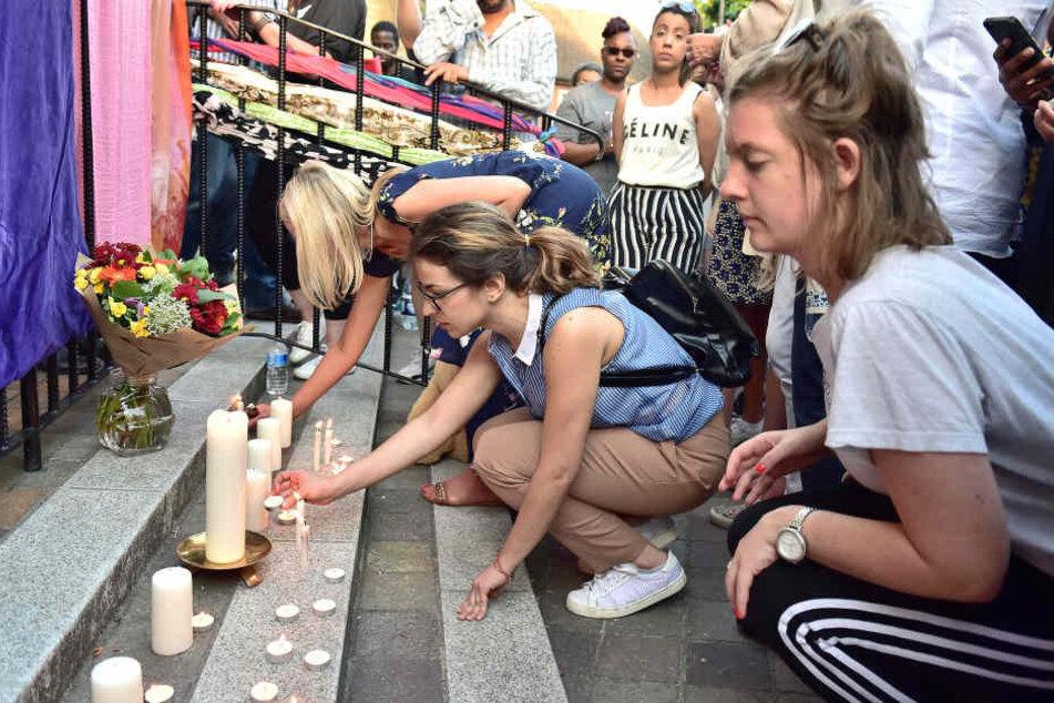 Menschen zünden im Stadtteil Notting Hill Kerzen an.