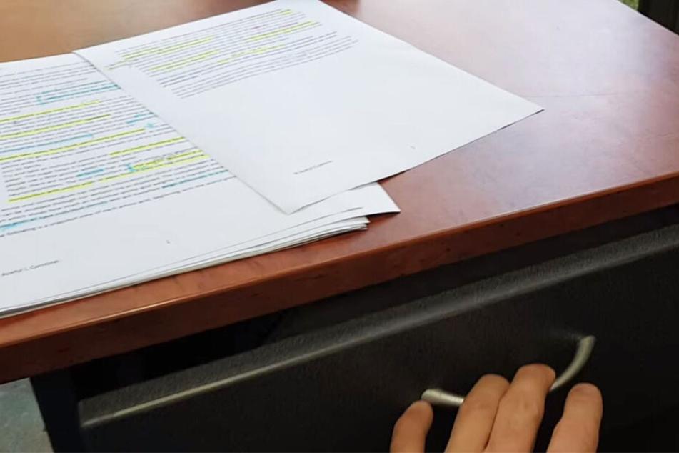 Angestellte öffnet ihre Schreibtisch-Schublade und fällt vor Schreck fast vom Stuhl