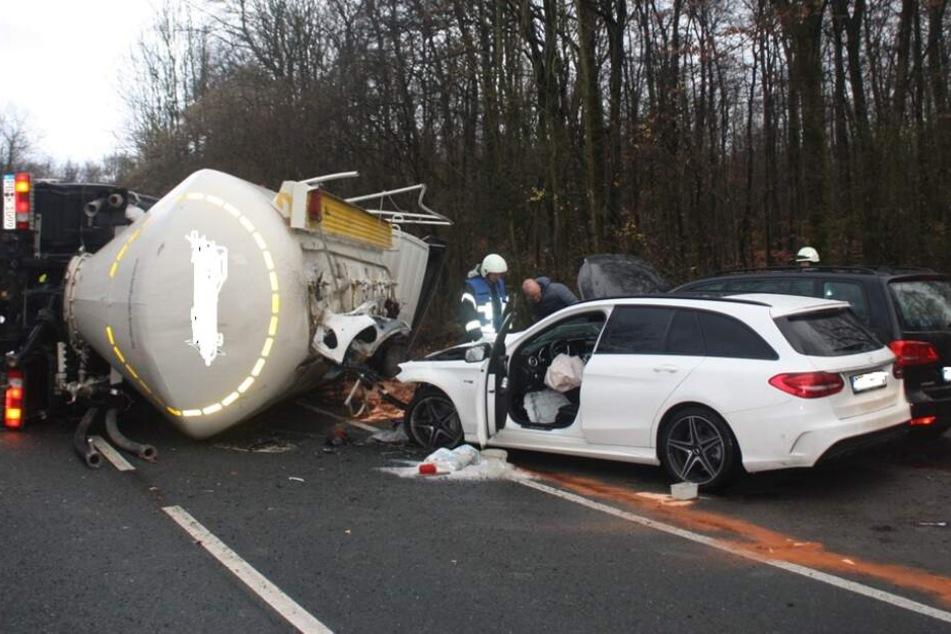 Lastwagen schleudert von Landstraße, kippt um und reißt Auto mit