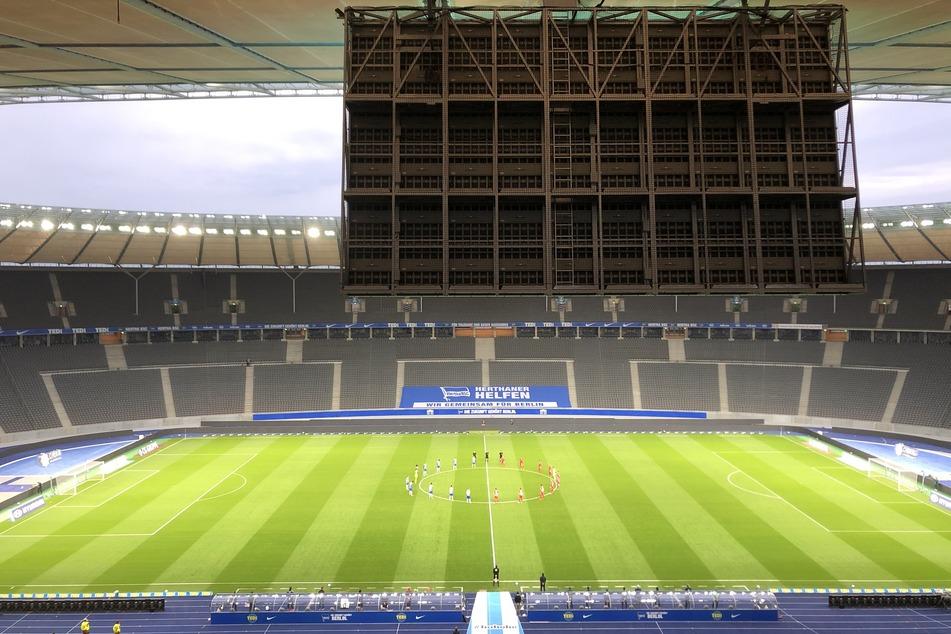 Die Spieler von Hertha BSC und 1. FC Union Berlin stehen auf dem Spielfeld im leeren Stadion