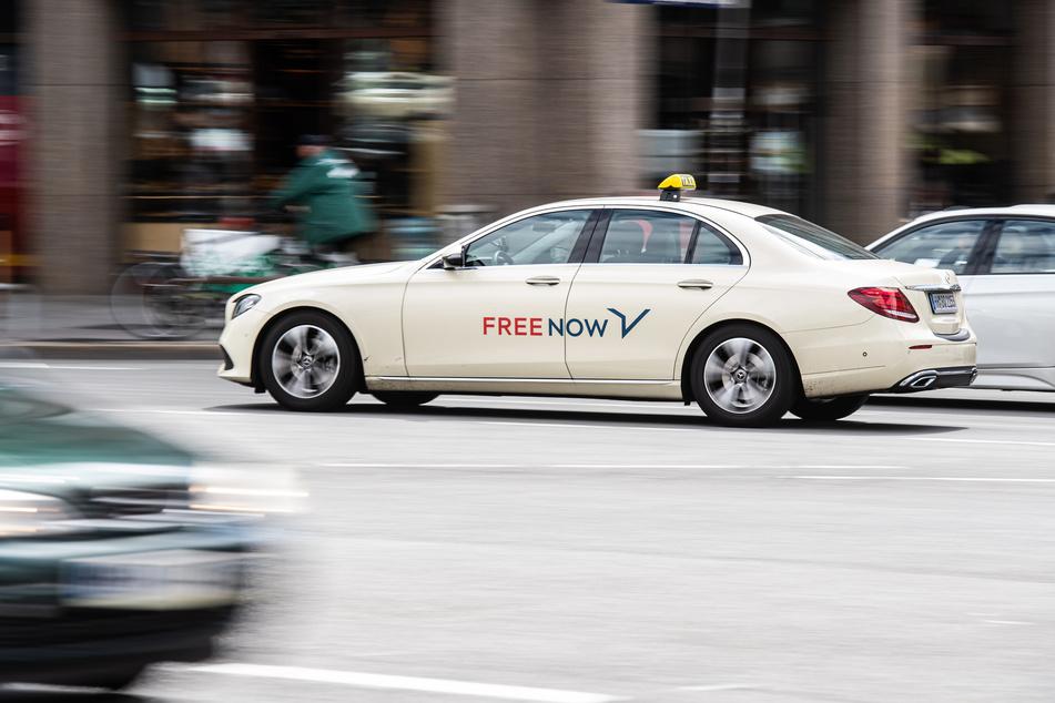 Ein Taxi des Taxi-Vermittlers Free Now (ehemals MyTaxi) fährt über eine Straße.