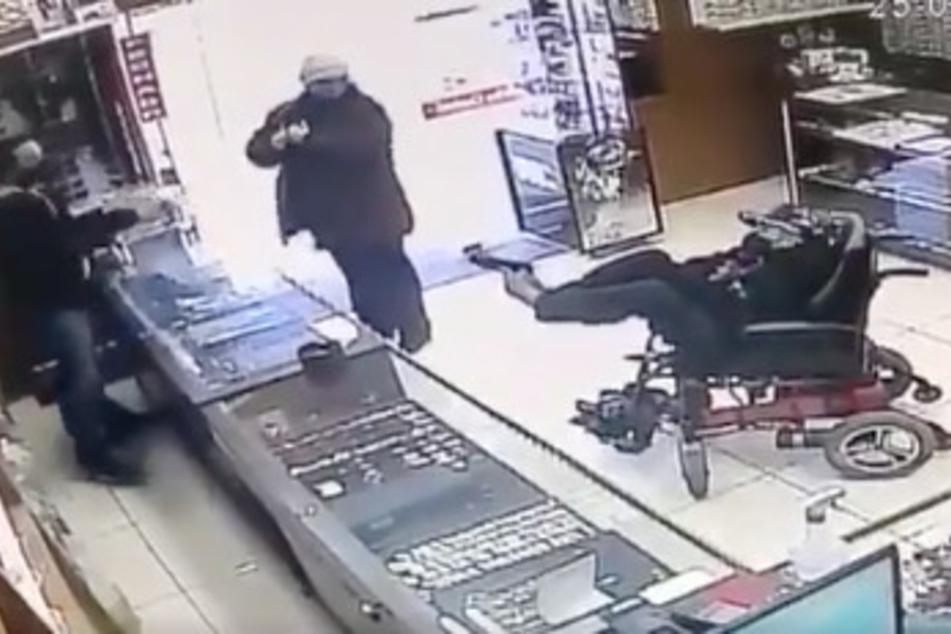 Der 19-Jährige richtet mit seinen Füßen eine Waffe auf den Verkäufer hinter dem Tresen.