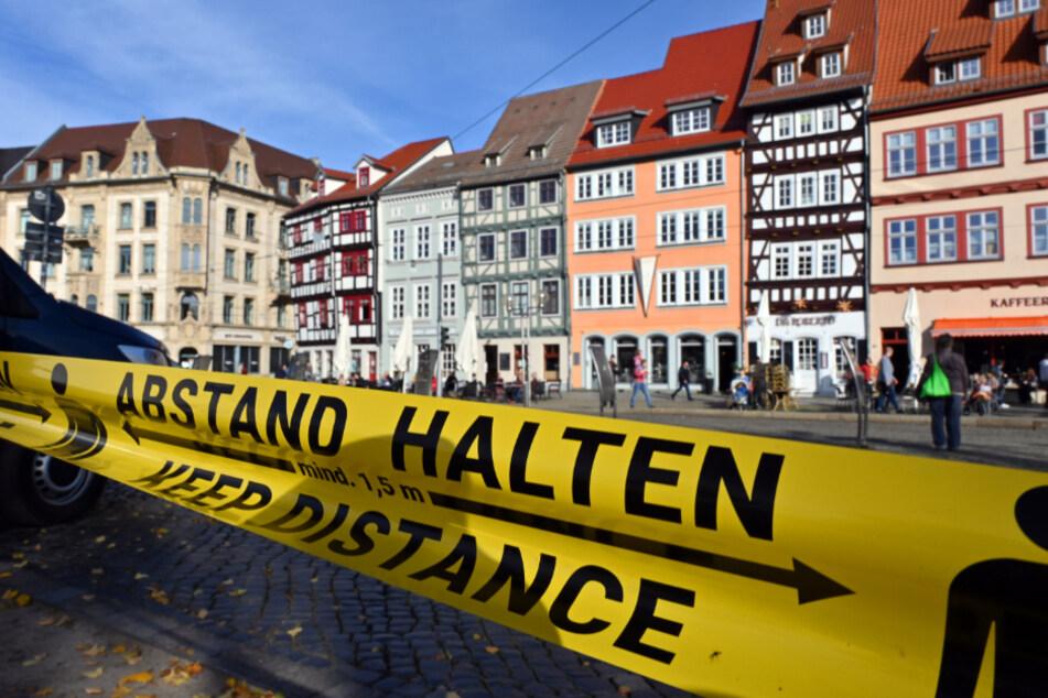"""""""Abstand halten!"""" in deutscher und englischer Sprache steht auf einem Flatterband am Domplatz inmitten der Erfurter Altstadt."""