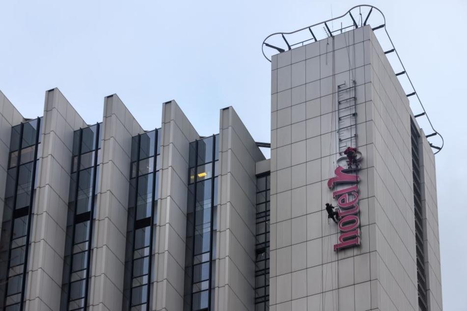 Bergsteiger demontieren den alten Schriftzug am Hotel.